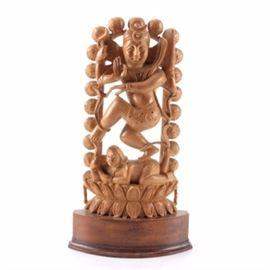 Nataraja Shiva Inspired Carved Sandalwood Figurine: An Indian inspired carved sandalwood figurine. This piece depicts the Hindu god Shiva as a dancer, or Nataraja, doing the Tandava dance. The figure is decorated with garlands of snakes and stand on a the back of a demon, which rests on a lotus-shaped base. There is an arch of fire behind the god and demon figures. There is a label to the underside.