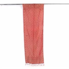Red Scarf: A red scarf. This scarf features a scrolling foliate and floral style design in shades of black and gold on a red base with a braided rope style border and guard border. This scarf also features a fringe at either end and is unmarked.