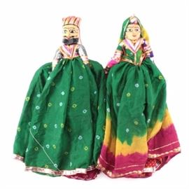 Reversible Wooden Dolls: A pair of reversible wooden dolls. This selection includes two wooden dolls who, when you turn them upside down, reveal a new doll. Both items include a female doll to one side, and a male doll to the other. The doll bodies are constructed from wood and include a red patterned fabric dress to one side, and a green patterned fabric dress to the other. No visible maker's marks.