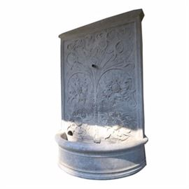Ornate Cement Fountain: A Sussex Wall Fountain ornate cement water fountain. The fountain is model FT-39, and is designed to be mounted to a wall. It has a backboard of decoratively patterned cement, with a bow front basin at the bottom. The fountain comes with instructions for installation and use, and includes a pump with cord. The model number of the Little Giant pump is PES-70.