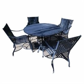 Metal Patio Table and Four Chairs: A metal patio table with four matching chairs. The patio set is constructed of steel, painted black. The chairs feature slat backs, and the table is round with a hole in the center for an umbrella pole, though no umbrella is included. The set is unmarked by the manufacturer.