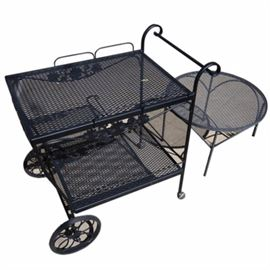 Metal Patio Bar Cart and Side Table: A metal patio bar cart and side table. The bar cart and table feature black painted metal frames, and expanded metal surfaces. The cart has two shelves and a side handle, with black metal floral details, and it rests on two casters and two wheels. The matching round side table has a metal frame and rests on four round, straight legs. No maker's marks.