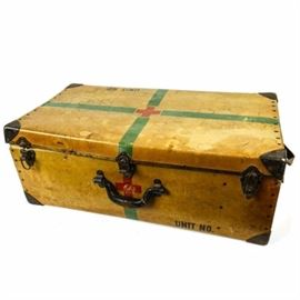 "World War II Era Red Cross Medical Trunk: A World War II era Red Cross medical trunk. The piece is constructed of a cardboard-like material, with metal corners and latches. The suitcase is brown, with a Red Cross logo to its center, with radiating green stripes. There are three latches and a handle on the case, marked ""USA Excelsior Stamford Conn"", and a side strap made of green webbing. The interior features one large main compartment and one smaller side compartment."