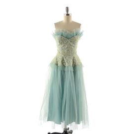 Circa 1950s Party Dress: A circa 1950s party dress. This aqua taffeta dress features a sweetheart neckline, fitted waist, and hidden back zip closure, with a cream lace overlay to the bodice and peplum, aqua tulle overlay and embellished with tiers of pleated tulle to the neckline and peplum. The interior is unlined, with boned support to the bodice, and unmarked.