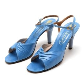 """Vintage H&M Rayne Wedgwood Jasperware Heels with Original Box: A pair of vintage H&M Rayne Wedgwood Jasperware high heels. These blue leather heels feature an open toe, sculptural pleated vamp and adjustable ankle straps with gold-tone buckle, sitting atop a bisque blue Jasperware heel with a cream Zephyr in bas-relief with a leather top piece. The leather insoles are stamped in gold luster ink, and the leather sole is stamped """"Made in England"""". Includes the original box."""