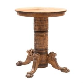 Tiger Oak Carved Bar Table: An antique tiger oak carved high top bar table. Having a high round top over a generous column and four carved lion head and paw feet.