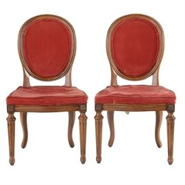 """Vintage Balloon Back Side Chairs: A pair of vintage, Victorian-style balloon back side chairs. These chairs have balloon backs and a serpentine apron with corner carved floral accents. They rest on tapered, reeded legs and are covered with a red velvet upholstery. Marked """"Davis Cabinet Co."""" on tags to the bottom."""