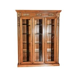 Neoclassical Revival Style Display Cabinet: A Neoclassical Revival style display cabinet. This piece features crown molding over applied molding details including rosette blocks, above a grouping of frame beveled glass panels, all flanked by carved column stiles. Two of the panels are doors and include escutcheons and open to reveal glass interior shelving. The cabinet sides have the same upper molding and feature a framed inlay detail surrounding figured and bookmatched veneers. The unit rests onto a plinth base. For a coordinating piece, see item 17STL012-299-7247.