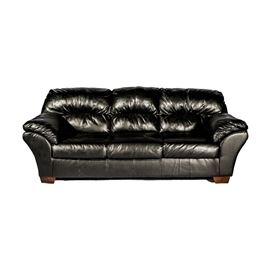 Black Leather Sofa: A black leather sofa. This three-seat sofa features tufting to its back and cushions on its arms. It rests on tapered square wooden feet.