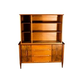 """Mid Century Modern Hutch by Stanley Furniture: A Mid Century Modern hutch by Stanley Furniture. This item features two shelves to its top, separated in two sections of complementary sizes. The base features three drawers with cup pulls to the center, flanked by two walnut burl veneered cabinet doors; each cabinet area has a vertical pull to the center and one shelf to the interior. It rises on tapered legs and is marked """"Distinctive Furniture by Stanley"""" to the interior of a drawer."""