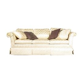 """Sofa & Chair Company Upholstered Sofa: An upholstered sofa by The Sofa & Chair Company. This piece has a rolled back with three cushions and rolled arms. It is upholstered in metallic cream-colored abstract fabric with a pleated skirt. Four throw pillows are included. The piece is marked """"The Sofa & Chair Company"""" under the seat cushions."""