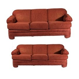 """Sofa & Chair Company Red Upholstered Sofas: A pair of sofas by The Sofa & Chair Company. Each sofa has three back cushions with rounded corners and rolled arms with slip covers. They are upholstered in dark red fabric and rest upon rounded, upholstered feet. They are tagged """"The Sofa & Chair Company"""" under their seat cushions."""