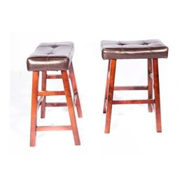 Leather Saddle Seat Stools: A pair of saddle seat bar stools with leather tops. Each item features a button-tufted brown leather seat which rises on four square legs in a cherry finish. They are unmarked.