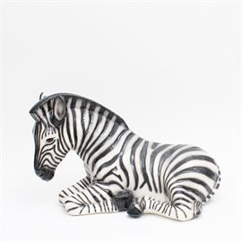 Ceramic Sitting Zebra Figure: A ceramic sitting zebra figure. The piece features a black and white glazed finish with painted brown details to the eyes. The item is unmarked.