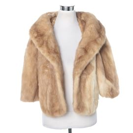 Vintage Mink Fur Cape: A vintage fur cape. This selection showcases a tan mink fur cape with a shawl collar. It is lined with a light brown sheen fabric. There are no visible brand labels.