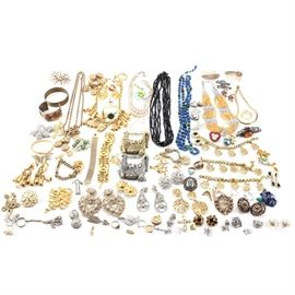Generous Selection of Jewelry Including Vintage Pieces and Kramer: An assortment of costume jewelry. Featuring over thirty pieces, this selection includes necklaces, bracelets, earrings, hair clips, brooches, rings, and more. Highlights include a DKNY gold tone bottle cap set, a pair of silver-tone foil back double dangle Kramer earrings and enamel hair clips, and a Coro charm bracelet and brooch.