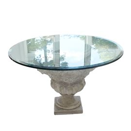 Grecian Inspired Pedestal Table With Glass Top: A Grecian inspired pedestal table with glass top. This table features a round, clear glass top resting on an urn shaped pedestal post terminating on a square base. The urn pedestal features scrolling handles with acanthus leaf detail throughout. There are no visible maker's marks.