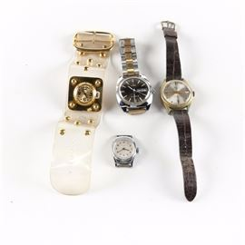 Wristwatches Including Timex and Vendome: A selection of wristwatches. This selection includes a gold tone Vendome wristwatch with a clear plastic band, a silver tone Timex wristwatch case, and a gold tone wristwatch with an alligator grain band. Also included, a silver tone Timex wristwatch with a chrome plated base metal bezel, stainless steel back, and a silver and gold tone band.