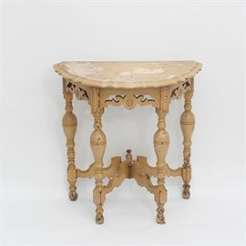 Carved Demilune Table: A vintage carved demilune table. This table features a demilune shape with a serpentine edge; its apron is pierced and carved with scrolling and circular shapes. It rises on four turned legs with toupie feet. They are connected by shape stretchers with a center urn finial. The piece has been painted in a tan color.