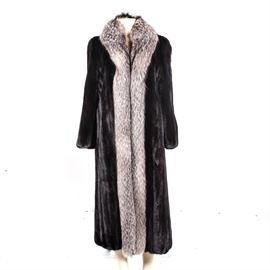 Mink and Fox Fur Coat: A women's long fur coat. This rich brown mink fur coat features a fox fur shawl collar and trim. The interior is lined in a chocolate brown satin fabric and is unmarked.