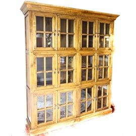 Oak China Cabinet: A French Provincial style oak frame glass front china cabinet. This unique design has three rows with two 2-door compartments on each layer. The doors open to reveal two shelves for storage. The unit has a light brown stain that highlights the grain pattern in the wood. The cabinet has a heavy crown molding on the top and a straight bottom molding.