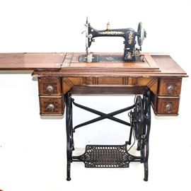 Antique Davis Sewing Machine and Table: An antique Davis sewing machine with table by Davis Sewing Machine Co. of Dayton, OH. This piece has a walnut and veneer frame that rests on a black cast iron base with a foot pedal and casters. The top folds out to the left, and the sewing machine can be lifted up. The table includes four small drawers to either side, one drawer to the middle with three compartments, reeded decoration to their fronts and brass pulls. Serial no. 755080.