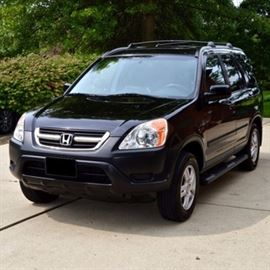 2004 Honda CR-V Crossover SUV: A black 2004 Honda CR-V crossover SUV, 5DR, 4WD EX model. This four wheel drive SUV is a 4-speed automatic and comes equip with a 2.4 liter, a 16 valve engine and anti-lock brakes. Exterior features include tinted windows to reflect heat, back privacy windows, four passenger power lock doors, a power moonroof, a remote control key entry system, roof racks and a tailgate mounted spare tire with cover. Interior features include black leather seats, power locks and windows, driver front and side passenger airbags, an AM/FM cassette and 6-disc CD changer and cruise control. Odometer reads 83,204 miles. VIN# is JHLRD78874C039951.