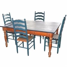 Farmhouse Dining Table and Four Ladderback Chairs: A farmhouse style dining room table and a set of four ladderback chairs. The dining table is made of wood with a painted blue surface. It features a simple skirt with faux drawers and knobs to each side and rests atop four turned table legs. The chairs feature country blue frames with woven seating. Two seats are woven in blue and cream, one in salmon and sage and a third features natural rush seating.