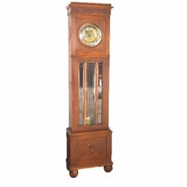 Vintage Mission Style Oak Tall Case Clock: An artisan crafted oak tall case clock. This clock features Mission design elements including an oak case with a reeded cornice and a brass face with black numerals. The case features a frame door with three beveled glass panels. When opened, it reveals a pendulum and two brass weights.