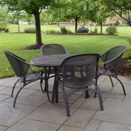 Mesh Patio Table and Chairs: A mesh patio dining table and a set of four chairs. The dining table is round with a mesh top and a center hole for an umbrella. The four chairs are also mesh and features comfortable curved backs with modern, curved legs.