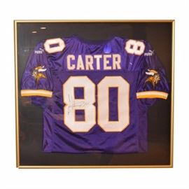 Autographed and Framed Cris Carter Minnesota Viking's Jersey: An autographed and framed Cris Carter Minnesota Viking's football jersey. This jersey is purple, white and gold. It includes Cris Carter's autograph on the jersey's number, 80 in black ink. The jersey is floating on a black mat presented under glass in a gold tone metal frame and wire to the verso for hanging.