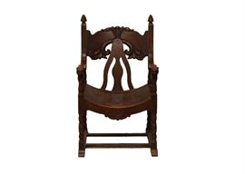 Antique Carved Wooden Throne Chair: An antique carved walnut wood throne chair. This dark walnut chair features a carved floral head rest, a cutout back rest with curved seat, two gently curved arms with lions heads to the hand rest, turned legs connected by side and center stretcher.