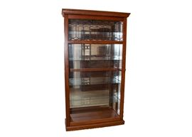 Lighted Curio Cabinet: A traditional lighted curio cabinet. This lovely cabinet features a wood frame in a warm cherry finish and a sliding lockable glass front door with decorative diamond and hexagon shaped metal piping to the top.The interior boasts four adjustable glass shelves with grooves for displaying plates and a mirrored back.