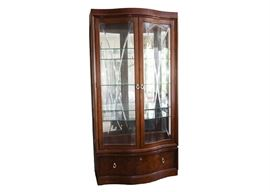 Thomasville Curio Cabinet: A Thomasville lighted curio cabinet. This mahogany finished cabinet has a serpentine front with beveled V-grooved bowed glass cabinet doors. The interior space features glass shelves, glass sides and a mirrored back. A burled finished bow front storage drawer beneath the cabinet doors has dovetail joints and silver-tone loop pulls.