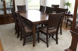 Broyhill Dining Table and Ten Chairs: A Broyhill dining table and ten chairs. This rectangular shaped table features a mahogany finish with inlaid top and end extensions resting on four cabriole style legs. Also included are ten mahogany finished side chairs with solid head and back rests, beige brushed suede style upholstered seats resting on four legs with stretchers to the sides.