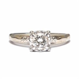 14K Platinum and Diamond Solitaire Engagement Ring: A 14K platinum, engagement ring setting that has a raised foliate detail at the shoulders and a prong-set diamond solitaire stone to center.