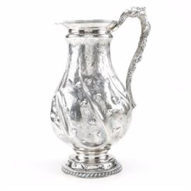 "Antique W. M. Gale & Son Sterling Silver Pitcher, Circa 1853-1855: An antique sterling silver pitcher. This piece was produced between 1853-1855 by the New York firm of W. M. Gale & Son. The jug with a swirled body is elaborately decorated with stippling, chased and repousse molding. The handle is molded with grapes and leaves in relief and a cartouche with the engraved inscription ""Bell Jones from F. N. B. Dec. 11th, 1855"" can be found in the center. There is a clover leaf and flower border above a gadrooned edge. The jug bears impressed factory marks reading ""W. M. Gale & Son New York"" together with a diamond, circle, and oval logo. The approximate weight is 31.925 ozt."