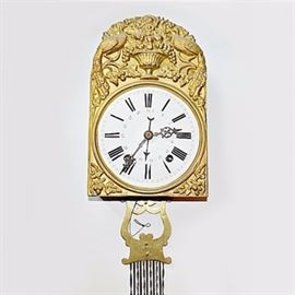 "1830s French Gilt Metal Mobilier Wag-on-the-Wall Clock: A 1830s French mobilier gilt metal ""wag-on-the-wall"" clock. This beautiful weight-driven clock is designed with a gilt metal case with arched top and elaborate repousse design featuring two peacocks to the sides with an urn overflowing with grapes and flowers to the center, with foliate and floral borders. The round clock face is in white enamel with black Roman numerals and openwork hands, with a center Arabic numeral band. Below the case is an openwork lyre form with vertical twisted rods connecting to a second openwork lyre form and below, a round gilt metal pendulum cover designed in a fruit and leaf pattern with a pineapple to the center. The clock's mechanism is driven by two cylindrical brass-encased weights. The clock is marked ""CN"" and ""Depose"" to the lower edge of the metal case."
