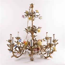 Eight Light Fixture Brass Chandelier With Porcelain Flower Accents: An eight light fixture brass chandelier with porcelain flower accents. The three-tiered brass chandelier features scrolled foliate arms, white candlesque light fixtures, and a gilded leaf motif with delicate porcelain flowers throughout in shades of yellow, cream, magenta, orange, and pale pink. Additional porcelain flowers are also included.