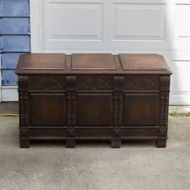 Carved Walnut Cedar Chest: A carved walnut cedar chest. The walnut chest features a rectangular frame, beveled paneled top, carved scrolled foliate designs, intricate turned columns along front, cedar lined interior, and square legs.