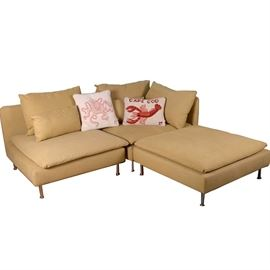 Scandinavian Style Two-Piece Sectional With Ottoman: A Scandinavian style two-piece sofa sectional with ottoman. The sofa sectional with ottoman features a low square back, removable seat and back cushions, two sea-themed accent pillows, round chrome legs, and is upholstered in a light mustard yellow cotton twill fabrication.