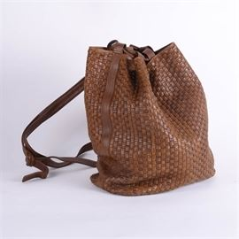 Vintage Fendi Brown Woven Leather Bucket Bag: A vintage Fendi brown woven leather bucket bag. The bag features a double leather strap drawstring closure, a brown interior lining with a zippered sidewall pocket and gold tone brand plaque. The bag can also function as a backpack. Made in Italy.