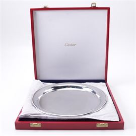 Cartier Pewter Plate: A pewter plate by Cartier. This plate feature a round body. The plate comes in a red storage case with latch closures.
