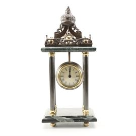 Indian Green Marble Mantel Clock: A green marble mantel clock made in India. It features a pointed crown finial with scroll designs to the pediment. It has a marble frame with a clock to the center. The clock is enclosed in lucite with brass trim. It has four marble pillars with brass caps and rests on a marble frame with brass ball feet. It is untested.