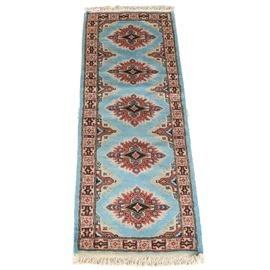 Hand-Knotted Pak-Kazak Carpet Runner: A hand-knotted Pak-Kazak carpet runner. This wool rug is rendered in a palette of cerulean, mauve, black, and taupe. It features an infinity pattern beginning with five starburst medallions arranged vertically over a cerulean field. Each medallion encloses a gul with out-pointing arrows amid abstract motifs. Framing the field are two borders, including an unresolved major border featuring alternating boxed florets and geometric Shirvan-style bracket motifs. Selvedges are overcast, the rug finishing at either end with ivory cotton warp fringe. It is unlabeled.