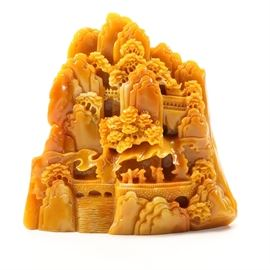 Orange Resin Sculpture of East Asian Landscape Scene: A table sculpture in orange resin. The decorative piece depicts a mountainous East Asian landscape scene, with trees, bridges, buildings and small figures overlooking a river to the base. The verso of the piece is carved to resemble a large stone. The item is unmarked.