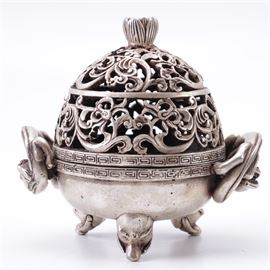 Chinese Metal Incense Burner: A Chinese metal incense burner. This piece features a pierced cover with a scrolled design and lotus finial. There are meander borders around the base of the cover and rim of the footed base. The base is flanked by two dragon shaped handles on either side. The underside is stamped with a seal mark.