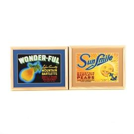 Framed Vintage Fruit Crate Labels for Wonder-Ful and Sun Smile Pears: A set of two mid-century offset lithograph fruit crate labels on paper, each with brightly colored graphics. Featured is a label for Wonder-Ful brand Lake County Mountain Bartlett pears from Upper Lake, California. The piece is matted in blue and presented under glass in a wooden frame with a sawtooth hanger to the verso. Also included is a label for Sun Smile brand Mountain Bartlett pears from Colfax, California. The label is matted in tan and presented under glass in a wooden frame with hanging wire to the verso.