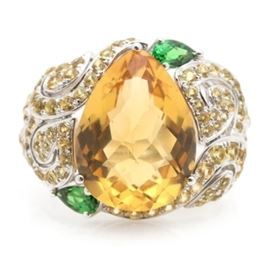 14K White Gold Citrine, Tsavorite Garnet, and Yellow Sapphire Statement Ring: A 14K white gold statement ring featuring a central citrine gemstone flanked by two offset tsavorite garnet accents. Pierced scrollwork shoulders contain 102 yellow sapphire embellishments leading to a brightly polished and tapered shank.