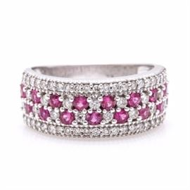 14K White Gold Ruby and Diamond Pave Set Band: A 14K white gold ruby and diamond pave set band. This band features two rows of alternating pave set rubies and diamonds sandwiched between two rows of smaller diamonds.